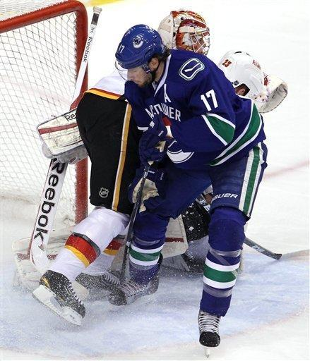 Vancouver Canucks center Ryan Kesler (17) tries to get a shot past Calgary Flames defenseman Scott Hannan (23) and goalie Leland Irving (37) during first-period NHL hockey game action at Rogers Arena in Vancouver, British Columbia, Friday, Dec, 23, 2011. (AP Photo/The Canadian Press, Jonathan Hayward)