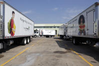 Container trucks are seen in the parking lot of the Houston Food Bank Wednesday, Oct. 14, 2020, in Houston. Distributions by the Houston Food Bank now average about 800,000 pounds (363,000 kilograms) daily after reaching the unprecedented 1 million pound mark for the first time in the spring, a level that the organization still delivers periodically. Before the coronavirus struck, the group's average daily distribution was 450,000 pounds (184,000 kilograms), said Houston Food Bank President Brian Greene. (AP Photo/Michael Wyke)