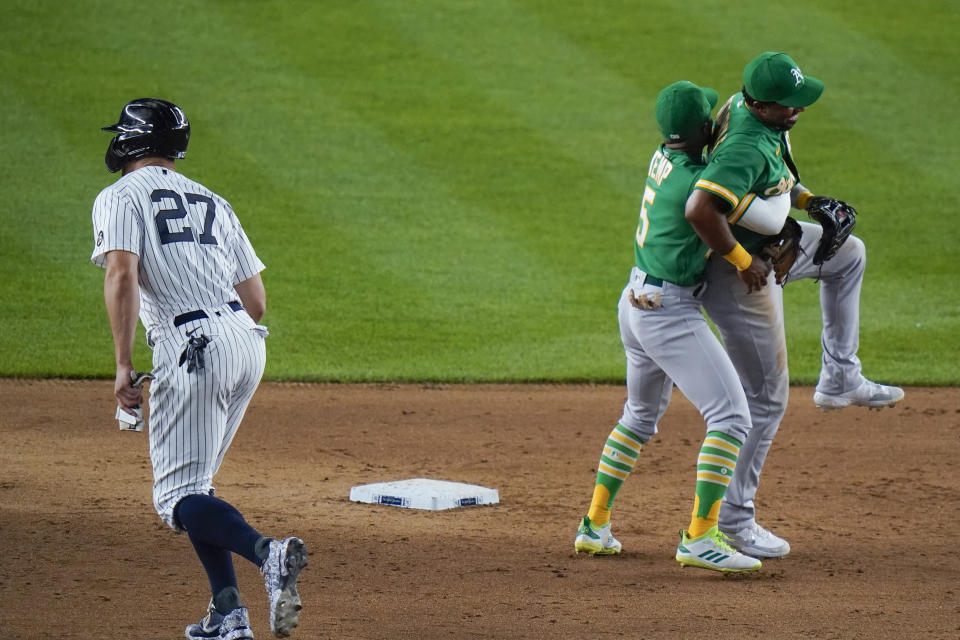 Oakland Athletics' Tony Kemp (5) hugs Elvis Andrus as New York Yankees' Giancarlo Stanton (27) leaves the field after a baseball game Friday, June 18, 2021, in New York. The Athletics won 5-3. (AP Photo/Frank Franklin II)