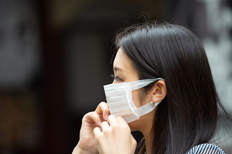 Asian woman putting on face mask (Photo: olaser via Getty Images)