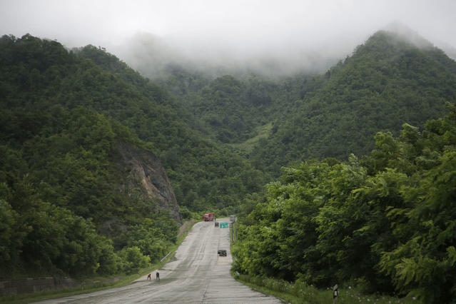 <p>Two men are dwarfed by a mountainous backdrop as they sweep rainwater off the Pyongyang-Wonsan highway on July 22, 2017, in North Korea. The Pyongyang-Wonsan highway is 172-kilometer-long or 107 miles long and it connects the North Korean capital to Wonsan, a port city on the Korean Peninsula. (Photo: Wong Maye-E/AP) </p>