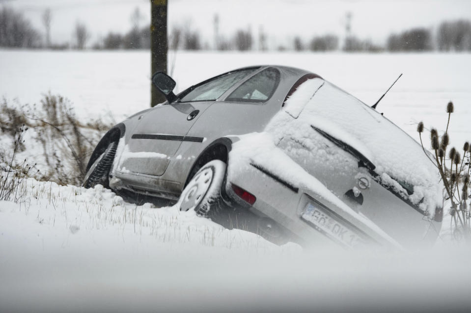A car lies in a ditch on a snow-covered country road in the district of Goettingen, Germany, Sunday, Feb. 7, 2021. (Swen Pfoertner/dpa via AP)