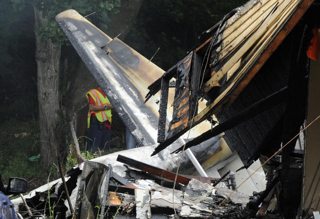 A responder surveys the scene of a small plane crash, Friday, Aug. 9, 2013, in East Haven, Conn. The multi-engine, propeller-driven plane plunged into a working-class suburban neighborhood near Tweed New Haven Airport, on Friday. (AP Photo/Fred Beckham)