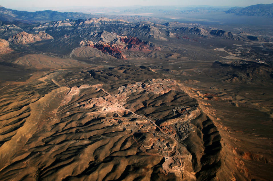 FILE - In this Oct. 11, 2016 photo, a gypsum mine owned by developer Jim Rhodes, who wants to develop housing on the site, is seen in the foreground while the Red Rock Canyon National Conservation Area is seen in the distance. Despite drought, cities in the U.S. West expect their populations to grow considerably in the coming decades. From Phoenix to Boise, officials are working to ensure they have the resources, infrastructure and housing supply to meet growth projections. In certain parts of the region, their efforts are constrained by the fact that sprawling metro areas are surrounded by land owned by the federal government. U.S. Sen. Catherine Cortez Masto wants to remedy the issue in Las Vegas by strengthening protections for some public lands while approving the sale of others to commercial and residential developers. (L.E. Baskow/Las Vegas Sun via AP, File)