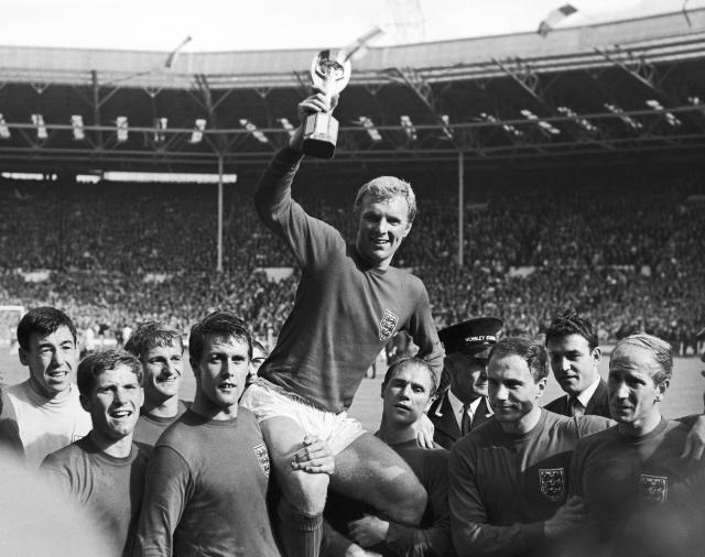 FILE - In this July 30, 1966 file photo, England's soccer team captain Bobby Moore, carried shoulder high by his teammates, holds aloft the Jules Rimet World Cup. England defeated West Germany 4-2 in the final, played at London's Wembley Stadium. From left to right, goalkeeper Gordon Banks, Alan Ball, Martin Peters, Geoff Hurst, Moore, Ray Wilson, George Cohen and Bobby Charlton. Peters, who scored one of England's goals in its victory over West Germany in the 1966 World Cup final, has died after a long battle with Alzheimer's disease. He was 76. Peters' family announced his death on Saturday, Dec. 21, 2019 via a statement through English soccer club West Ham, saying he passed away peacefully in his sleep. (Bippa via AP, file)