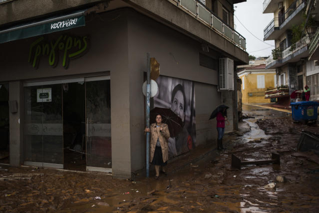 <p>Women holding umbrellas stand next to a damaged shop, in a flooded street of Mandra, northwest of Athens, on Nov. 15, 2017, after heavy overnight rainfall. (Photo: Angelos Tzortzinis/AFP/Getty Images) </p>