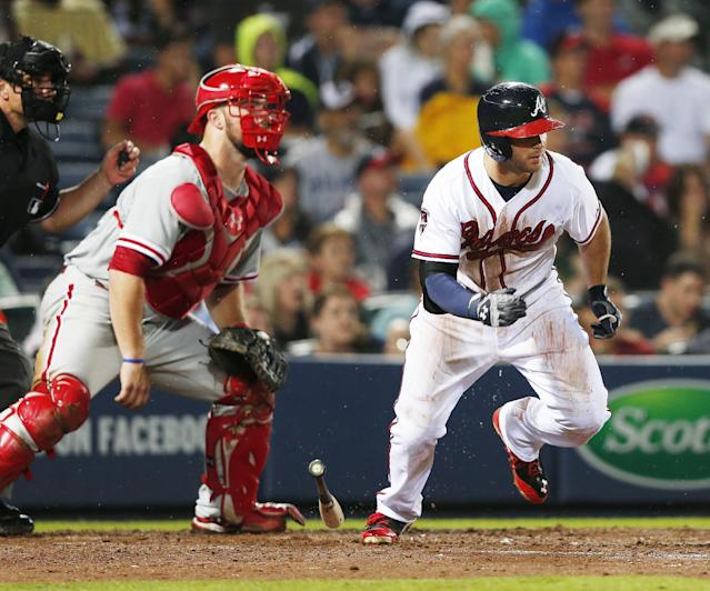 Atlanta Braves' Tommy La Stella (7) runs after hitting an RBI single in front of Philadelphia Phillies catcher Cameron Rupp during the fifth inning of a baseball game in Atlanta, Friday, July 18, 2014. (AP Photo/John Bazemore)