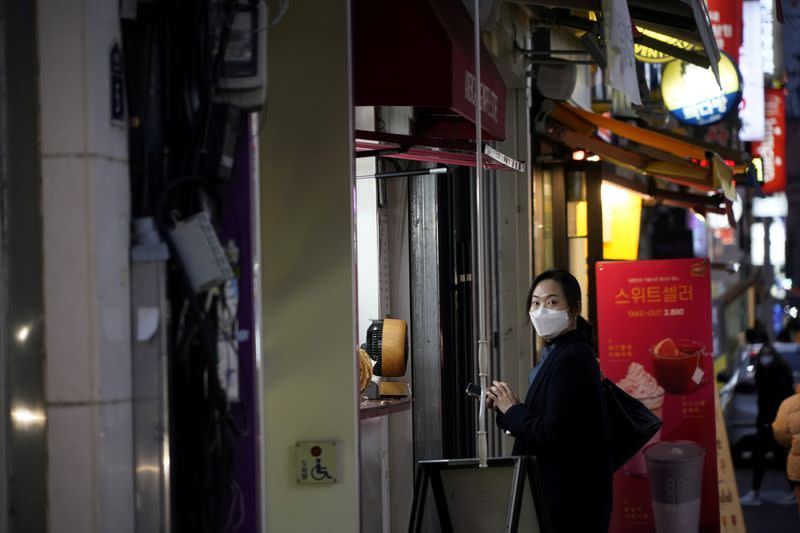 A woman wearing a mask to prevent contracting the coronavirus waits for her food at Dongseong-ro shopping street in central Daegu