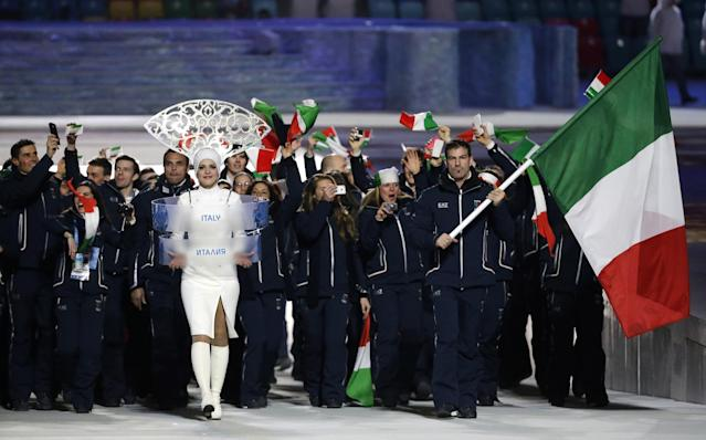Armin Zoeggeler of Italy carries the national flag as he leads the team during the opening ceremony of the 2014 Winter Olympics in Sochi, Russia, Friday, Feb. 7, 2014. (AP Photo/Mark Humphrey)