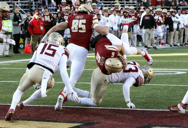 Boston College quarterback Dennis Grosel (6) dives over Florida State linebacker Amari Gainer for a touchdown in the second half of an NCAA college football game, Saturday, Nov. 9, 2019, in Boston. (AP Photo/Bill Sikes)