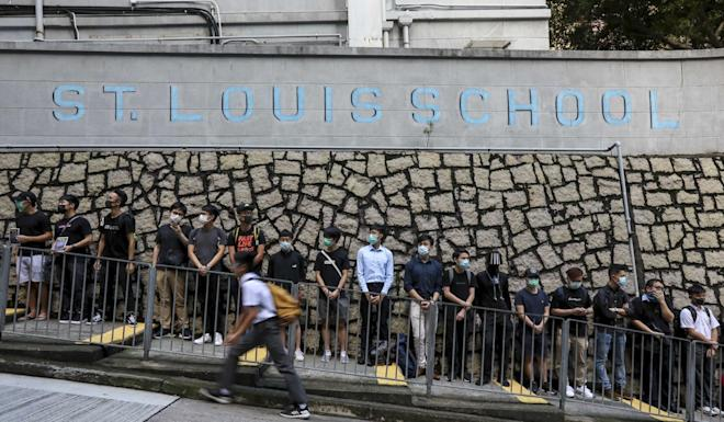 Alumni and students of St Louis School stand in support of students taking part in the class boycott. Photo: Felix Wong