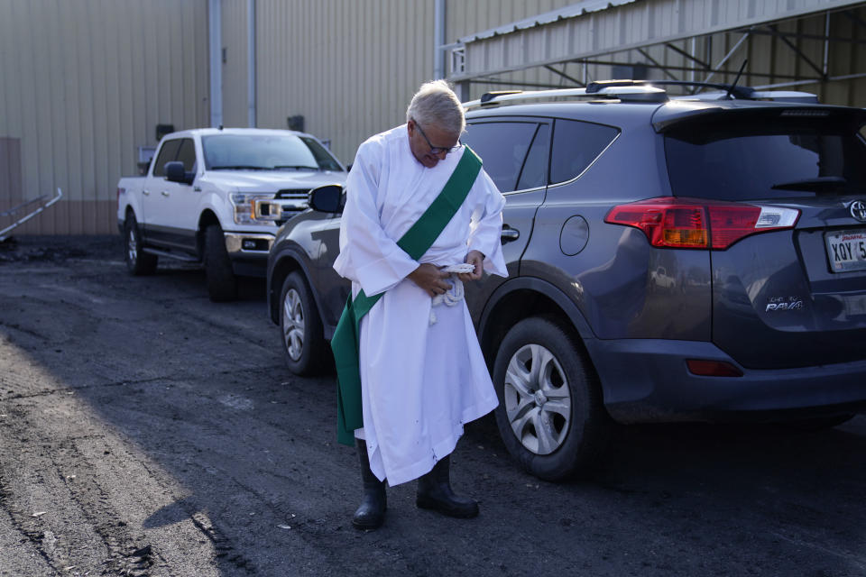 Deacon Ted Cain prepares to celebrate a Mass in a parking lot in the aftermath of Hurricane Ida, Sunday, Sept. 5, 2021, in Jean Lafitte, La. The service was held in a parking lot after St. Anthony Catholic Church was flooded in the hurricane. (AP Photo/John Locher)