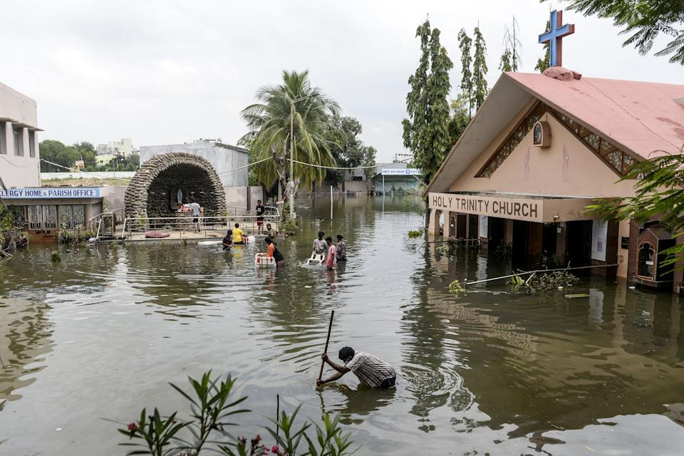 TOPSHOT - Parishioners carry material from the flooded Holy Trinity church following heavy rains in Hyderabad on October 15, 2020. (Photo by NOAH SEELAM / AFP) (Photo by NOAH SEELAM/AFP via Getty Images)