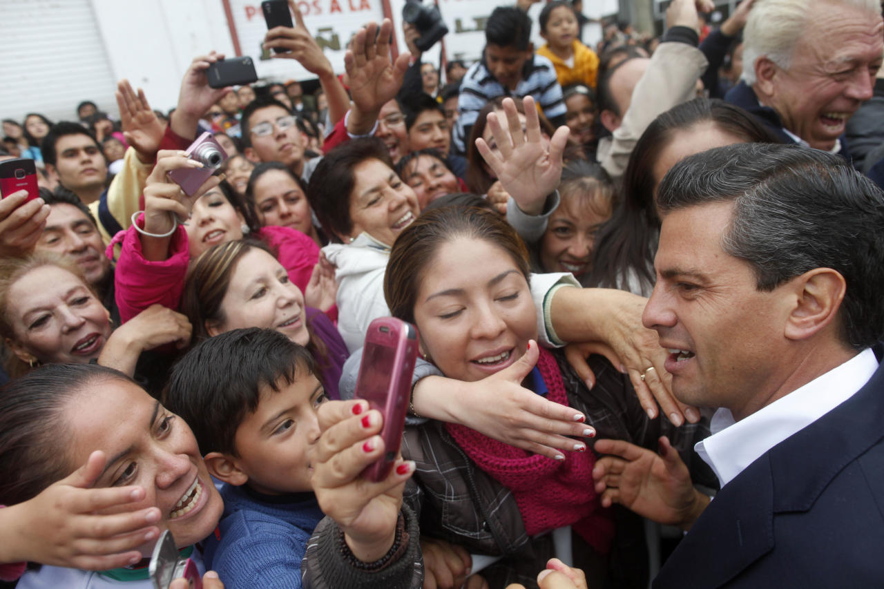 Enrique Pena Nieto, right, presidential candidate for the Revolutionary Institutional Party (PRI) greets supporters after casting his vote during general elections in Atlacomulco, Mexico, Sunday, July 1, 2012. Mexico's more than 79 million voters head to the polls Sunday to elect a president, who serves one six-year term, as well as 500 congressional deputies and 128 senators. (AP Photo/Esteban Felix)