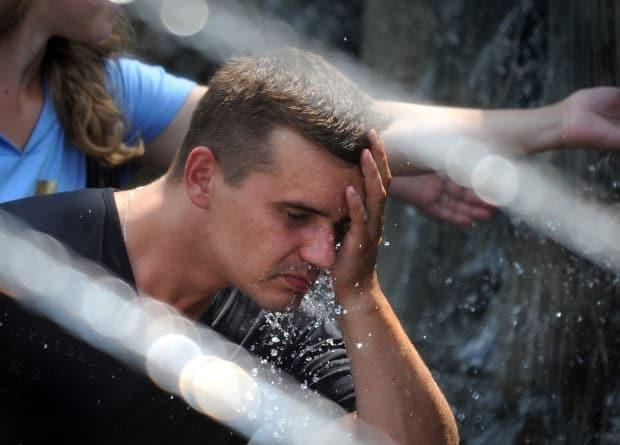A man refreshes himself in a fountain in central Moscow on July 20, 2010, amidst a prolonged heat wave.  (Alexander Nemenov/AFP - image credit)