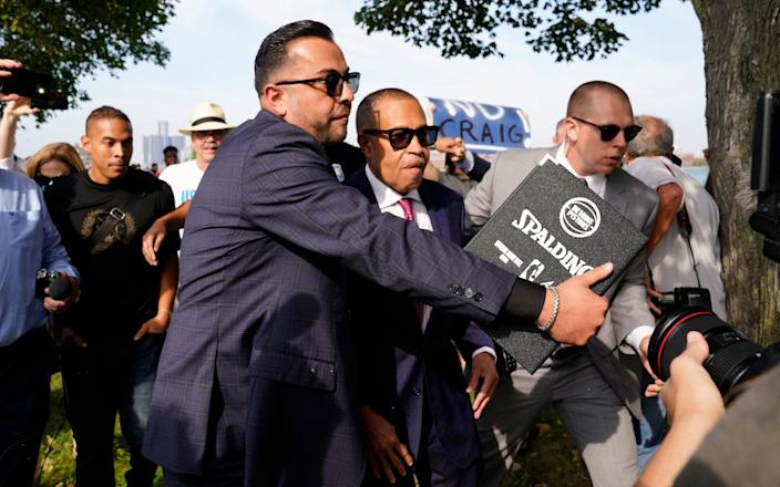 A security detail escorts former Detroit Police Chief James Craig from protesters before he could officially announce his run for Michigan governor as a Republican candidate on Tuesday in Belle Isle, Mich.