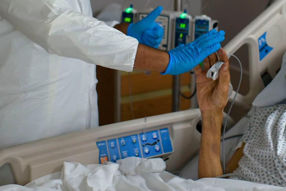 A healthcare worker high-fives a patient in the Covid-19 Unit at United Memorial Medical Center in Houston, Texas, July 2, 2020.