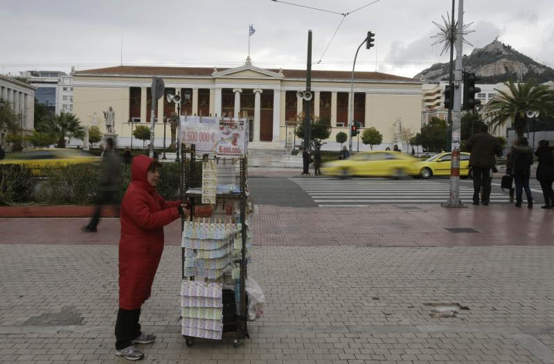 A lottery ticket vendor holds her stand in front of the University of Athens, Tuesday, Dec. 17, 2013. Greece's central bank has joined the government in predicting that the country's economy will grow in 2014 following a savage six-year recession but cautioned about the impact of a heated political rivalry ahead of elections in May. (AP Photo/Thanassis Stavrakis)