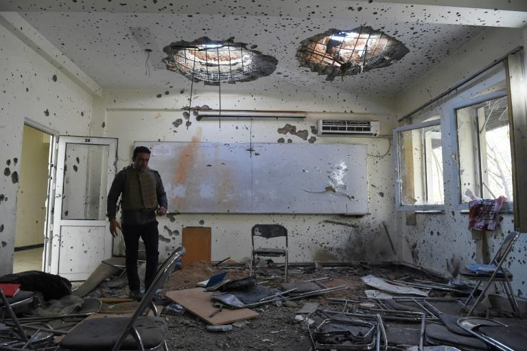 A journalist walks inside a damaged classroom a day after gunmen stormed Kabul university