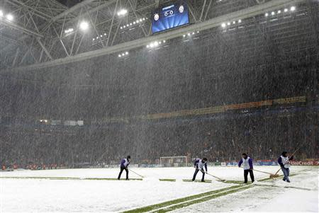 Workers rush to clean the snow from the pitch after the Champions League soccer match between Galatasaray and Juventus was paused for 20 minutes due heavy snowfall in Istanbul December 10, 2013. REUTERS/Murad Sezer