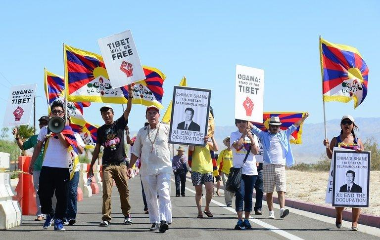 "Protesters shout slogans in a cordoned off protest zone across from the venue for talks between US President Barack Obama and his Chinese counterpart Xi Jinping in the California desert community of Rancho Mirage, California, on June 7, 2013. Several hundred protesters jeered Xi, including members of the banned Falungong spiritual movement and Tibetans who chanted, ""China, get out of Tibet!"""