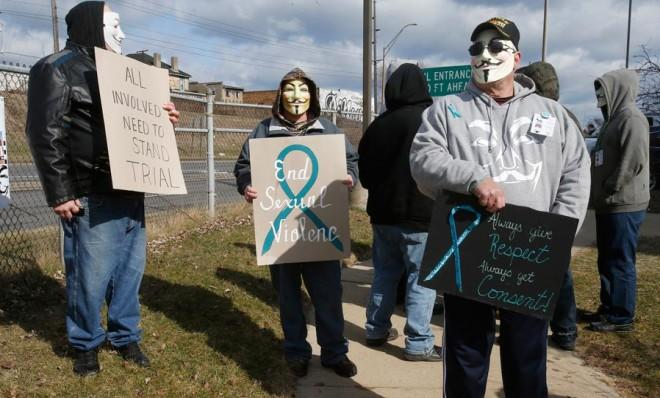 A group of protesters wearing Anonymous-associated Guy Fawkes masks stand outside the juvenile court in Steubenville, Ohio, on March 14.