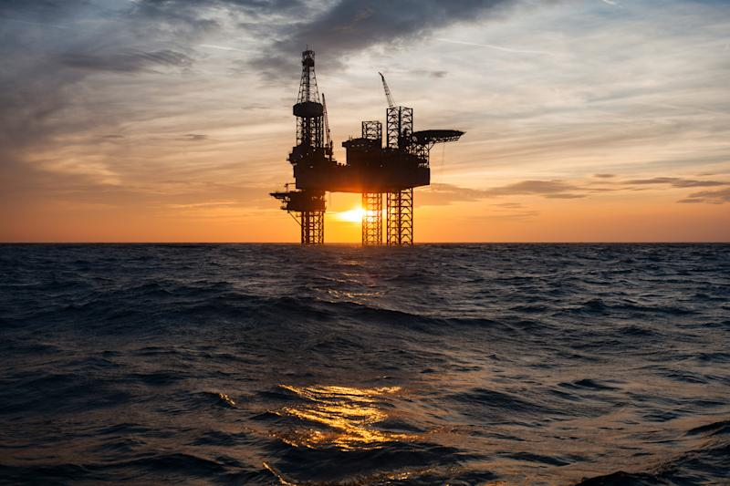 Silhouette of an offshore oil drilling rig with the sun low in the sky