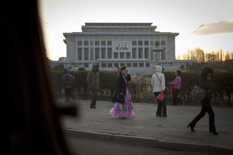 Seen through a car window, a woman dressed in traditional attire, center, rubs her face after participating in an official cultural event while another, right, talks on her mobile phone as they walk down a street at dusk in Pyongyang, North Korea, Thursday, April 11, 2013. (AP Photo/Alexander F. Yuan)