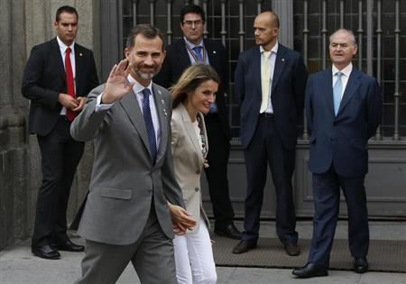 "Spain's Princess Letizia and her husband, Spain's Crown Prince Felipe, walk away after she collected money donations for the Spanish Red Cross during ""Fiesta de la Banderita"" in Madrid"