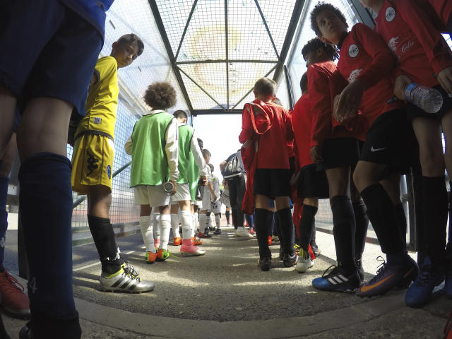 In this Saturday, May 5, 2018 photo, children line up in a stadium tunnel before taking the pitch for the Torcy Cup, in Torcy, east of Paris, France. The tournament is organized by the amateur club US Torcy, in the Paris suburb, where France midfielder Paul Pogba played when he was a teenager. Not all the money that will change hands after the World Cup, when clubs trade players who distinguish themselves on footballs biggest stage, will line the pockets of selling clubs, agents and the players themselves. A sliver of the wealth will also trickle down to footballs grassroots, to unpretentious, volunteer-run clubs where kids take first steps toward their dreams of making a career in the sport. (AP Photo/John Leicester)