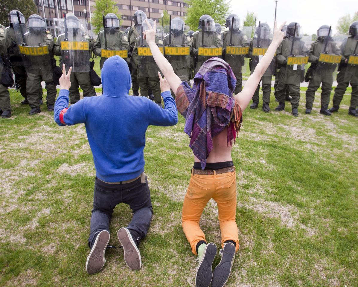 Students protesting against tuition hikes kneel in front of a line of Quebec Provincial Police at the Lionel Groulx college Tuesday, May 15, 2012 in Ste. Therese, Quebec, Canada. About one-third of post-secondary students in Quebec are boycotting classes in a protest against tuition hikes that has lasted more than three months. What started as a battle over a $325-a-year fee hike appears to have morphed into a broader struggle over the role of the state, the legitimacy of protest tactics, and the boundaries of authority. (AP Photo/The Canadian Press, Ryan Remiorz)