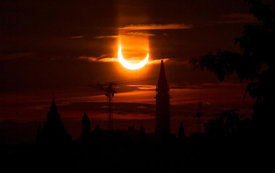 An annular solar eclipse rises over construction cranes and the Peace Tower on Parliament Hill in Ottawa, Canada.