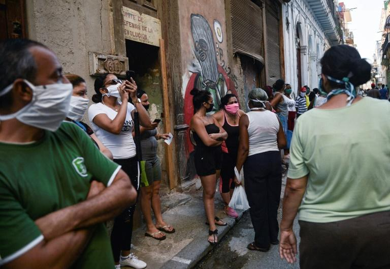 People wear face masks as they queue to buy food in Havana on May 19, 2020, amid the new coronavirus pandemic. US President Donald Trump has ramped up tensions with the island nation after a relaxation during the Obama years (AFP Photo/YAMIL LAGE)