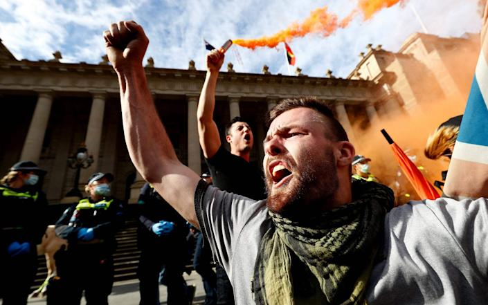 An anti-lockdown protester shouts slogans during a rally on the streets of Melbourne - CON CHRONIS /AFP