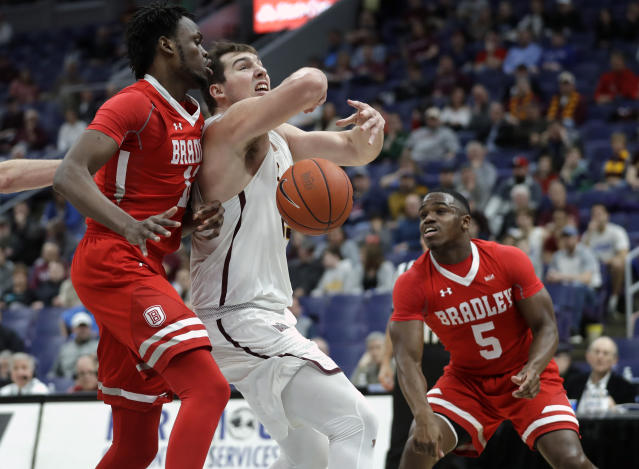 Loyola of Chicago's Cameron Krutwig, center, loses control of the ball as Bradley's Koch Bar and Darrell Brown (5) defend during the first half of an NCAA college basketball game in the semifinal round of the Missouri Valley Conference tournament, Saturday, March 9, 2019, in St. Louis. (AP Photo/Jeff Roberson)
