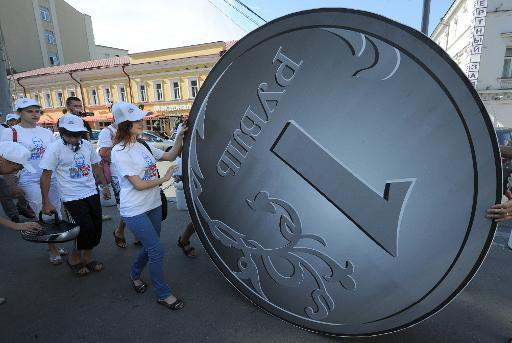 """Members of a social network group """"I Really Like Putin"""" perform in front or a two-meter Russian Ruble coin  in Moscow on August 18,  2011, during their action in support of Russia's currency"""