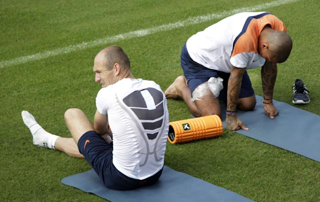 Netherlands players Arjen Robben and Nigel de Jong talk next to the pitch during a training session of the Netherlands in Rio de Janeiro, Brazil, Wednesday, July 2, 2014. The Netherlands player their quarterfinal of the 2014 soccer World Cup against Costa Rica on July 5 in Salvador. (AP Photo/Michael Corder)
