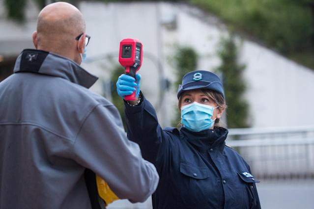 A security guard scans the temperature of an employee of a recently reopened automobile manufacturer in Turin, Italy. (Getty Images)