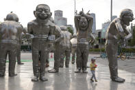 A child plays around sculptures outside a residential area in Beijing on Saturday, June 5, 2021. (AP Photo/Ng Han Guan)