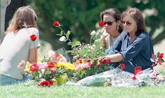 <p>Murder victim Nicole Brown Simpson's mother Juditha (R), and sisters Denise (C) and Tanya (L) sit next to her grave surrounded by flowers, in Lake Forest, Calif., on June 12, 1994, the one-year anniversary of the murder of Simpson and her friend Ronald Goldman. (Photo: Marilynn Young/AFP/Getty Images) </p>
