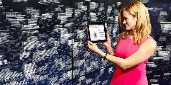A woman holding up a tablet in front of a wall with a digital data display.