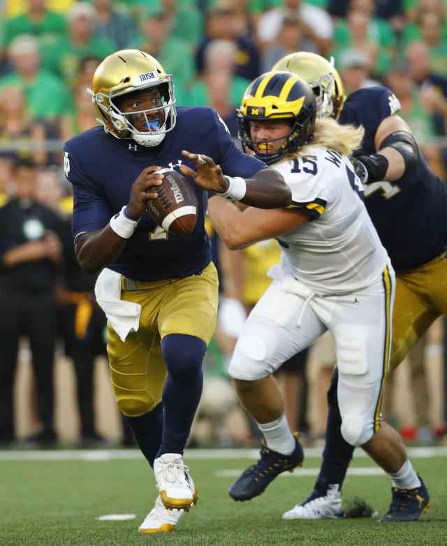 Notre Dame quarterback Brandon Wimbush (7) is chased out of the pocket by Michigan defensive lineman Chase Winovich (15) in the first half of an NCAA football game in South Bend, Ind., Saturday, Sept. 1, 2018. (AP Photo/Paul Sancya)