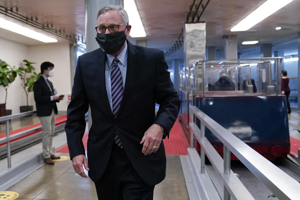 """FILE - In this Feb. 12, 2021, file photo Sen. Richard Burr, R-N.C., walks on Capitol Hill in Washington on the fourth day of the second impeachment trial of former President Donald Trump. Of the seven Republicans, Burr's vote to convict Trump was the most unexpected in the moment, and there were gasps in the chamber as he stood up declared his position. When the Capitol was attacked, Burr said in the statement, Trump """"used his office to first inflame the situation instead of immediately calling for an end to the assault."""" (AP Photo/Susan Walsh, File)"""