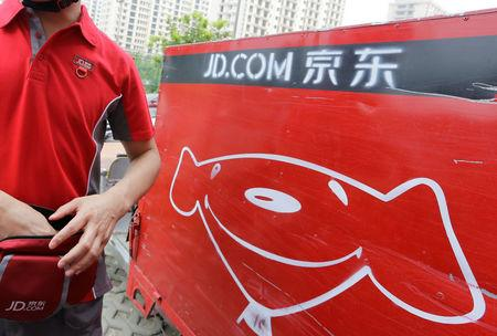 JD.com delivery tricycle is seen next to a delivery man in Beijing
