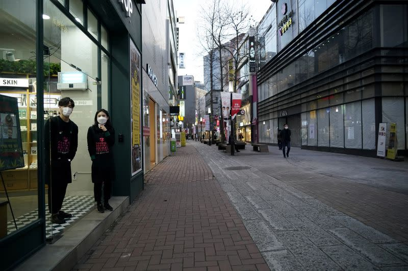 Shopkeepers wearing masks to prevent contracting the coronavirus wait for a customer at Dongseong-ro shopping street in central Daegu
