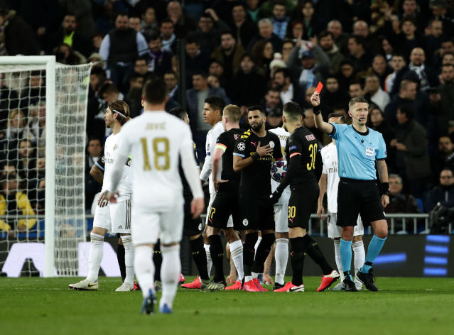 Referee Daniele Orsato, right, shows a red card to Real Madrid's Sergio Ramos, left, during the Champions League, round of 16, first leg soccer match between Real Madrid and Manchester City at the Santiago Bernabeu stadium in Madrid, Spain, Wednesday, Feb. 26, 2020. (AP Photo/Manu Fernandez)