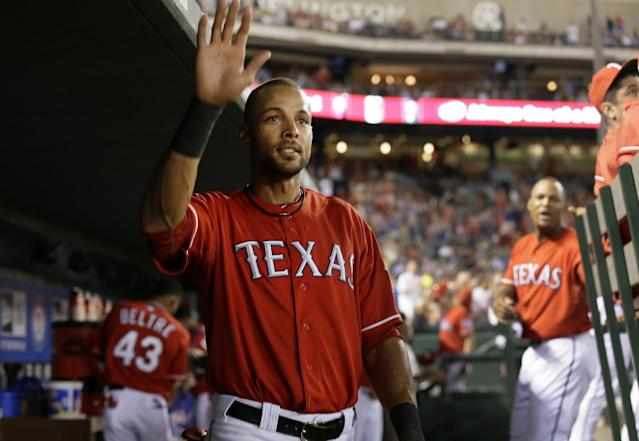Texas Rangers' Alex Rios (51) stands in the dugout as he acknowledges cheers from fans after it was announced over the public address system that with his sixth-inning triple, Rios hit for the cycle in a baseball game against the Houston Astros, Monday, Sept. 23, 2013, in Arlington, Texas. (AP Photo/Tony Gutierrez)
