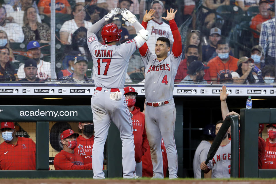 Los Angeles Angels designated hitter Shohei Ohtani (17) and Jose Iglesias (4) high five at the dugout after Ohtani's home run during the eighth inning of a baseball game against the Houston Astros Sunday, April 25, 2021, in Houston. (AP Photo/Michael Wyke)