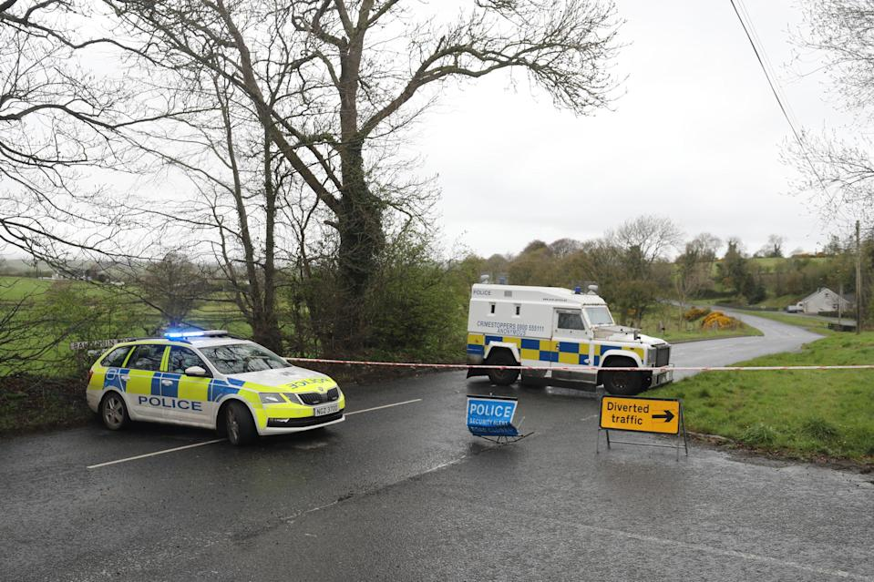 PSNI vehicles block a road after the explosive device was found in Dungiven (PA)