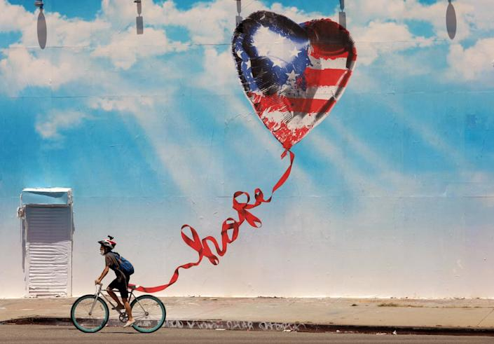 "A cyclist rides past a mural of a heart-shaped U.S. flag balloon with a long ribbon that curls to spell out ""hope."""